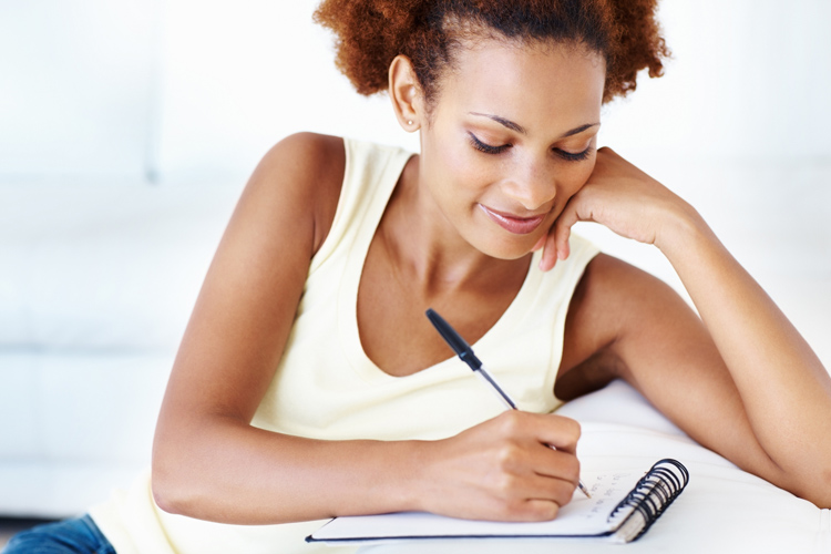 African American woman writing on notepad